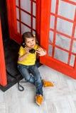 Kleines Mädchen, das in der Telefonzelle sitzt Lizenzfreies Stockfoto