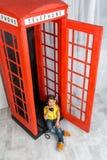 Kleines Mädchen, das in der Telefonzelle sitzt Lizenzfreie Stockbilder