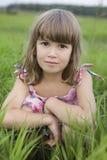 Kleines Mädchen, das in der Wiese sitiing ist Lizenzfreies Stockbild