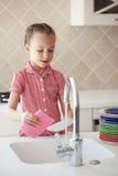 Kleines Mädchen, das die Teller wäscht Stockbild