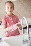 Kleines Mädchen, das die Teller wäscht Lizenzfreies Stockbild