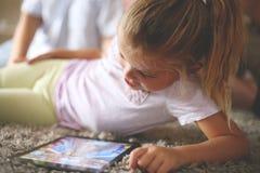 Kleines Mädchen, das digitale Tablette verwendet lizenzfreie stockfotografie