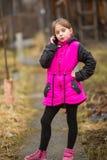 Kleines Mädchen, das draußen auf Mobile spricht nave Stockbild