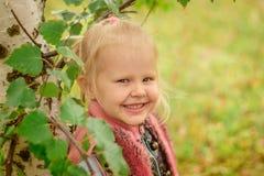 Kleines Mädchen, das draußen an der Birke lächelt Lizenzfreie Stockbilder