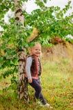 Kleines Mädchen, das draußen an der Birke lächelt Stockfotografie