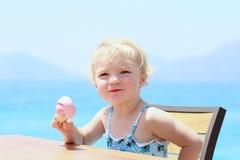 Kleines Mädchen, das draußen Eiscreme isst Lizenzfreie Stockbilder