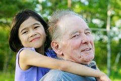 Kleines Mädchen, das draußen ihren Großvater, Verschiedenartigkeit umarmt Stockbild