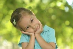 Kleines Mädchen, das draußen im Sommer aufwirft Stockfoto
