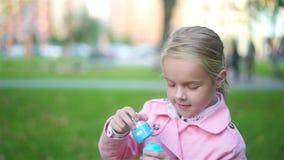 Kleines Mädchen, das draußen mit Seifenblasen spielt stock video footage