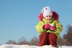 Kleines Mädchen, das draußen am Schnee sitzt Stockbilder