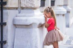 Kleines Mädchen, das draußen Verstecken auf Straße in Paris spielt Stockfotografie