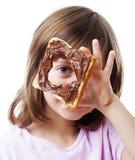 Kleines Mädchen, das durch Brot mit Schokoladenbutter schaut Stockfotos