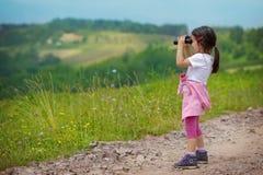 Kleines Mädchen, das durch die Ferngläser im Freien schaut Stockbild