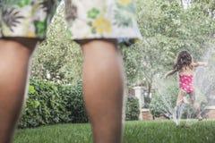Kleines Mädchen, das durch ein Besprühung wie Vater aufgepasst, niedriger Abschnitt springt Lizenzfreies Stockbild