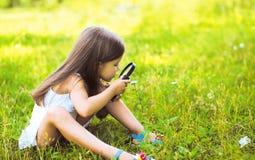 Kleines Mädchen, das durch ein Vergrößerungsglas schaut Lizenzfreies Stockfoto