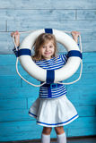 Kleines Mädchen, das durch einen Rettungsring schaut Stockfotos