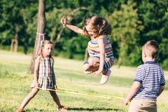 Kleines Mädchen, das durch das Gummiband, spielend mit anderen Kindern springt stockbild