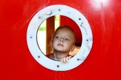 Kleines Mädchen, das durch Kreisfenster schaut Lizenzfreies Stockfoto