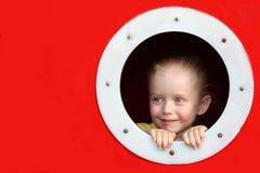 Kleines Mädchen, das durch Kreisfenster schaut Lizenzfreie Stockbilder
