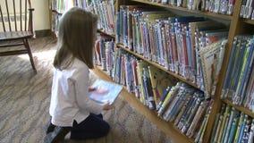 Kleines Mädchen, das durch Reihen von Jugendbüchern schaut stock video footage