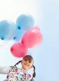 Kleines Mädchen, das ein Bündel Ballone anhält stockbild