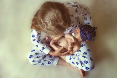 Kleines Mädchen, das ein Baby hält Stockfoto