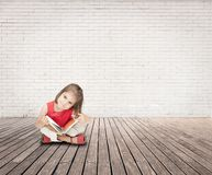 Kleines Mädchen, das ein Buch auf einem Raum liest stockfoto