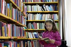 Kleines Mädchen, das ein Buch in der Bibliothek liest stockbild