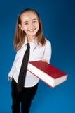 Kleines Mädchen, das ein Buch gibt Stockfoto