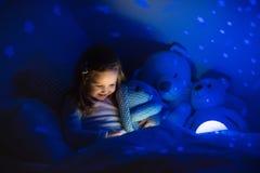 Kleines Mädchen, das ein Buch im Bett liest Lizenzfreie Stockfotos