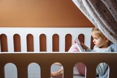 Kleines Mädchen, das ein Buch im Schlafzimmer liest stockfotografie