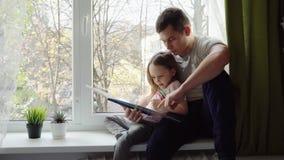 Kleines Mädchen, das ein Buch mit seinem Vater liest stock footage