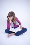 Kleines Mädchen, das ein Buch sitzt auf dem Boden liest Stockfotos