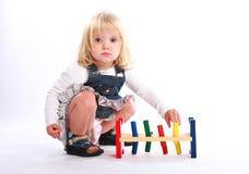 Kleines Mädchen, das ein buntes Spielzeug spielt Stockfoto