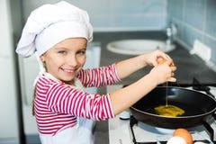 Kleines Mädchen, das ein Ei knackt Lizenzfreies Stockfoto
