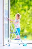 Kleines Mädchen, das ein Fenster im Reinraum wäscht Stockbild