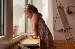 Kleines Mädchen, das ein Fenster untersucht Stockbilder