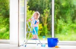 Kleines Mädchen, das ein Fenster wäscht Lizenzfreies Stockfoto