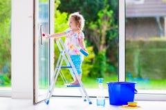 Kleines Mädchen, das ein Fenster wäscht Stockbilder
