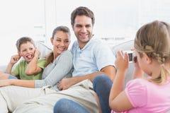 kleines m dchen das ein foto ihrer familie auf der couch macht stockfotografie. Black Bedroom Furniture Sets. Home Design Ideas