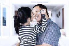 Kleines Mädchen, das ein Gesicht ihres Vaters zeichnet Stockbild