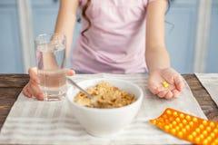 Kleines Mädchen, das ein Glas Wasser und Vitamine hält stockfotos