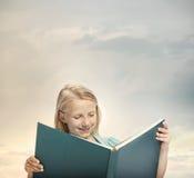 Kleines Mädchen, das ein großes Buch liest Lizenzfreie Stockfotos