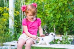 Kleines Mädchen, das ein Häschen auf einer Bank streichelt stockfotografie