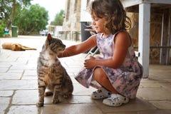 Kleines Mädchen, das ein Kätzchen streicht lizenzfreie stockbilder