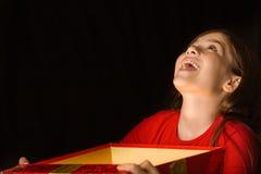 Kleines Mädchen, das ein magisches Weihnachtsgeschenk öffnet Stockbild