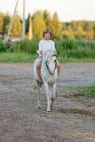Kleines Mädchen, das ein Pferd reitet Lizenzfreies Stockbild