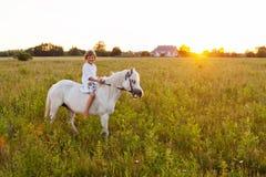 Kleines Mädchen, das ein Pferd reitet lizenzfreies stockfoto