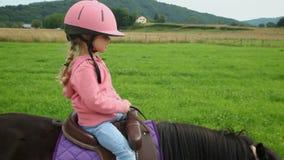 Kleines Mädchen, das ein Pony in der Landschaft reitet stock video