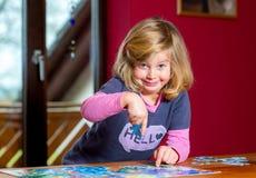 Kleines Mädchen, das ein Puzzlen tut Stockfotografie